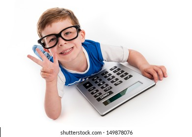 Toddler boy lying on the floor with a big calculator and holding up three fingers.