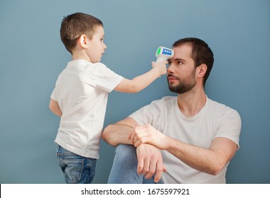 toddler boy is measuring his father's body temperature using infrared thermometer on a blue background