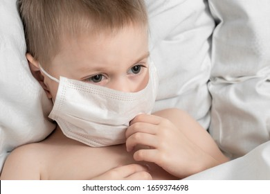 Toddler boy with a medical mask on his face lying in bed/ Coronavirus Safety Warning/2019 nKoV Coronavirus originating in Wuhan, China/ Close-up portrait