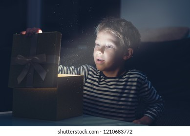Toddler boy opening golden Christmas gift box with magic dust and light coming from the present, retro toned image.