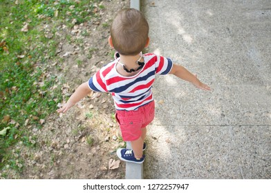 Toddler boy performing as tightrope walker on garden curb. Training balance for kids concept