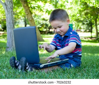 toddler boy playing with laptop