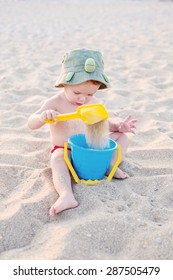 Toddler boy playing on the beach in summer