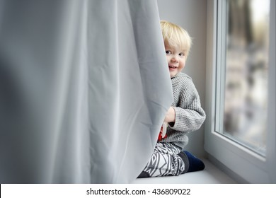 Toddler boy playing on the window sill at home