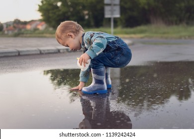 Toddler boy playing in puddle outdoors after rain wearing rubber boots, crouching and touching water. Outdoors, natural lighting, no retouch, matte filter.
