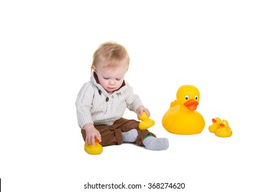 Toddler boy playing with rubber ducks isolated on white