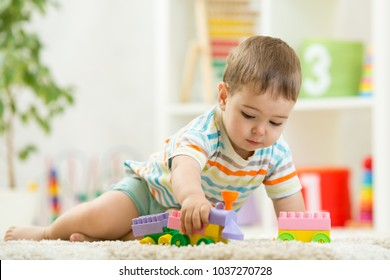 Toddler boy playing with toys on a white carpet at home