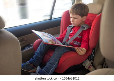 Toddler boy reading book in child car seat. Entertainment in the car for children concept