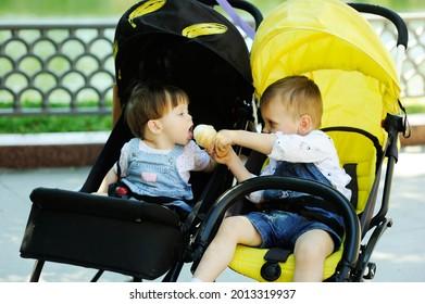 Un enfant en bas âge partage de la glace avec sa petite soeur pendant son trajet en double poussette dans le parc d'été de la ville