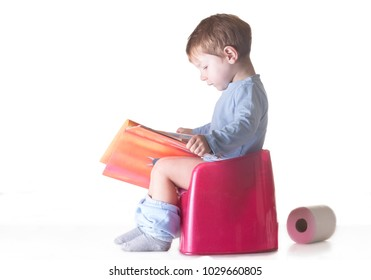 Toddler boy sitting on chamber pot reading story book. Potty training concept