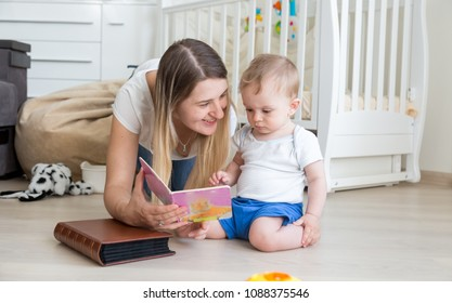 Toddler boy sitting on floor with mother and reading book