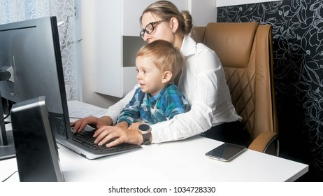 Toddler boy sitting on mothers lap working in office