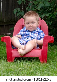 toddler boy sitting  in a red chair outdoors