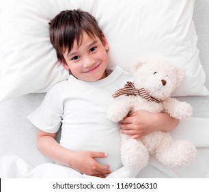 Toddler boy sleeping on his back holding plush teddy bear