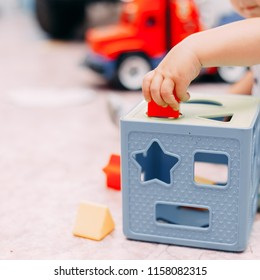 Toddler boy solves sorter puzzleToddler boy finds block with matching hole shape playing in child room