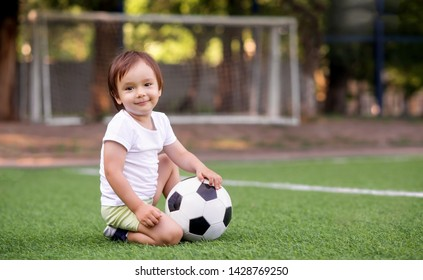 Toddler boy in sports uniform sitting with soccer ball at football field outdoors in summer day. Goalposts (soccer nets) in background. Kid sports and active childhood concept. Copy space