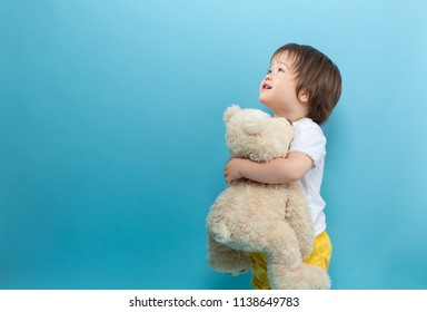 Toddler boy with a teddy bear on a blue background