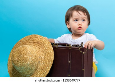 Toddler boy travel theme with a suitecase and a hat on a blue background