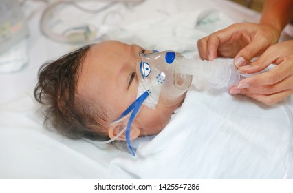 Toddler boy using nebulizer to cure asthma or pneumonia disease . Sick baby boy rest on patients bed and has inhalation therapy by the mask of inhaler. Respiratory Syncytial Virus (RSV).