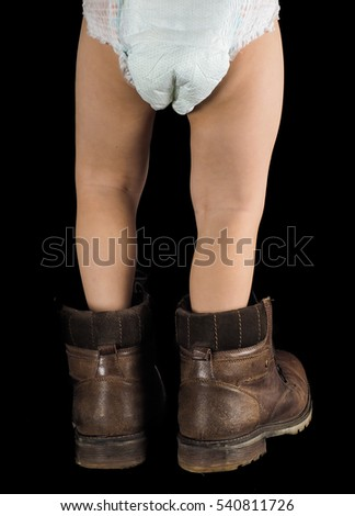 Toddler boy, walking away in fathers over sized brown leather boots, isolated on black