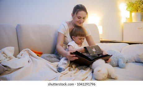 Toddler boy watching family photo album with his mother in bed at night