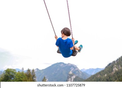 Toddler boy wearing blue t-shirt swinging on a swing at playground on beautiful alps mountain