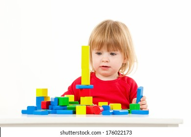 A toddler builds a tower with colorful blocks.