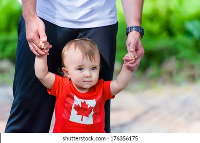 Toddler in Canada Flag shirt walking assisted by his father. Room for copy space.