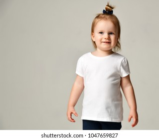Toddler child baby girl kid standing in white free text space t-shirt on grey background
