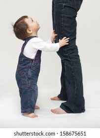 Toddler child, boy or girl, standing by mother's legs, looking up
