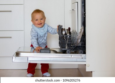 Toddler child, boy, helping mom, putting dirty dishes in dishwasher at home, modern kitchen