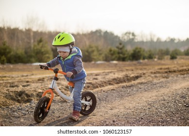 Toddler child boy riding on he's first bike without pedals. He's standing on road and he is getting ready to move. Sport concept: kids ride bicycle; first bike; active toddler kid playing and cycling.
