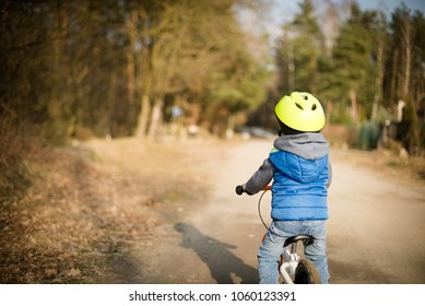 Toddler child boy riding on he's first bike without pedals. He's standing on road and looks ahead. Sport concept: kids ride bicycle; first bike; active toddler kid playing and cycling outdoors.
