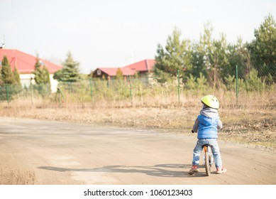 Toddler child boy riding on he's first bike without pedals. He's standing on road and waiting for something. Sport concept: kids ride bicycle; first bike; active toddler kid playing and cycling.