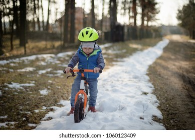 Toddler child boy riding on he's first bike without pedals. He's wades in the snow. Sport concept: kids ride bicycle; first bike; active toddler kid playing and cycling outdoors.
