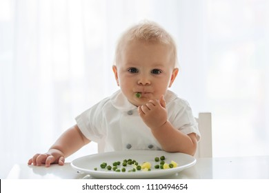 Toddler child, cute boy in white shirt, eating pea at home, back lit