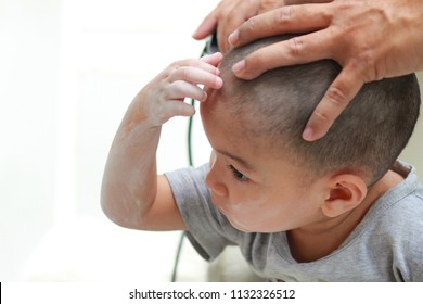 Toddler child getting his first haircut, with electric hair clipper.Handsome Asian boy stay calm while get skinhead stye hair cut.