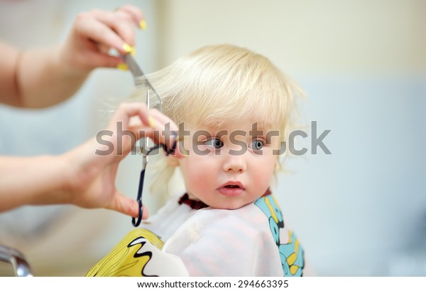 Toddler child getting his first haircut
