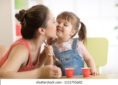 Toddler child girl is having healthy breakfast. Her mother is kissing her with love. Child is sitting at table and eats yoghurt