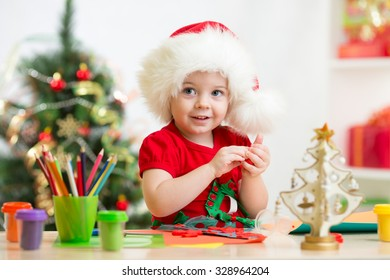 Toddler child girl making by hands christmas decorations