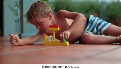 Toddler child playing by himself with buillding blocks outside during summer day