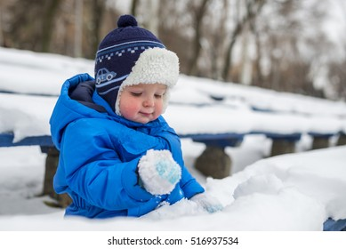 Toddler child playing in a snow in winter. baby playing with snow. baby playing with snow. baby playing with snow
