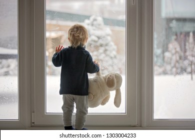 Toddler child standing in front of a big french doors, leaning against it looking outside at a snowy nature, holding teddy toy
