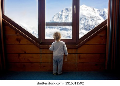 Toddler child standing in front of a big french doors, leaning against it looking outside at a snowy nature, playing with toys