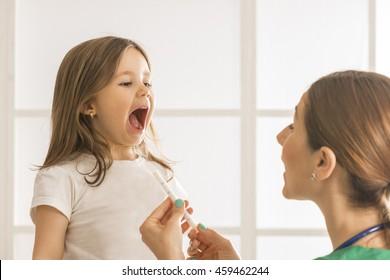 Toddler child take an oral medical suspension with syringe. Young female doctor giving little girl medicine