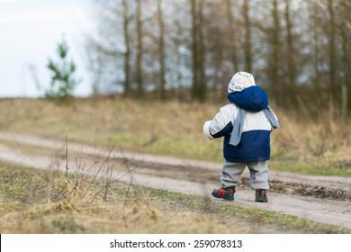 toddler child walking by rural sandy road