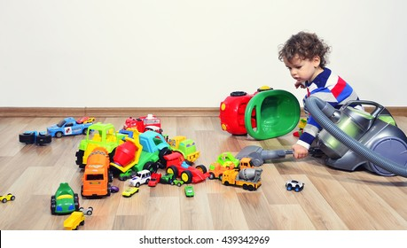 Toddler cleaning the messy room full of toys with a vacuum cleaner. Lots of toys, many cars piled on the floor