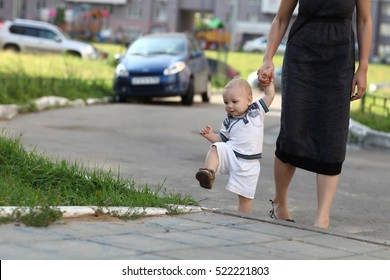 Toddler climbing on sidewalk with mother's support