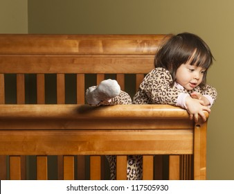 Toddler climbing out of her crib.