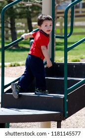 Toddler climbing up steps at a playground, making sure mom is watching